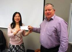 Miao Fan, 惠灵顿分会联合会长,给全国会计 Chris Goodwin 呈上给何明清纪念奖学金的支票,2014年7月